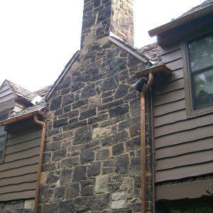 Stone chimney on side of wood house