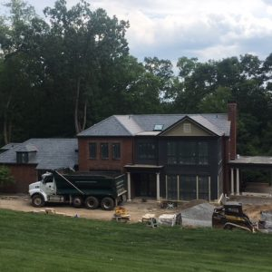 A large house with a dump truck out front